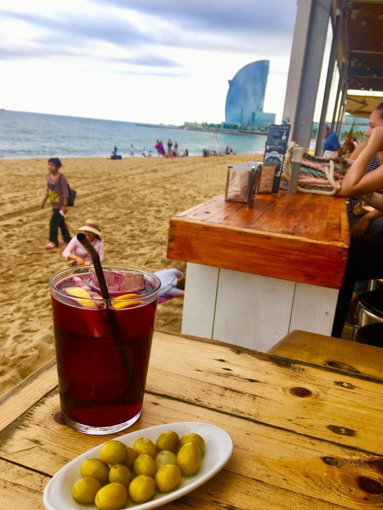 Blick von einem Strandcafé auf das Hotel W in Barcelona. Im Vordergrund: Sangria und Oliven