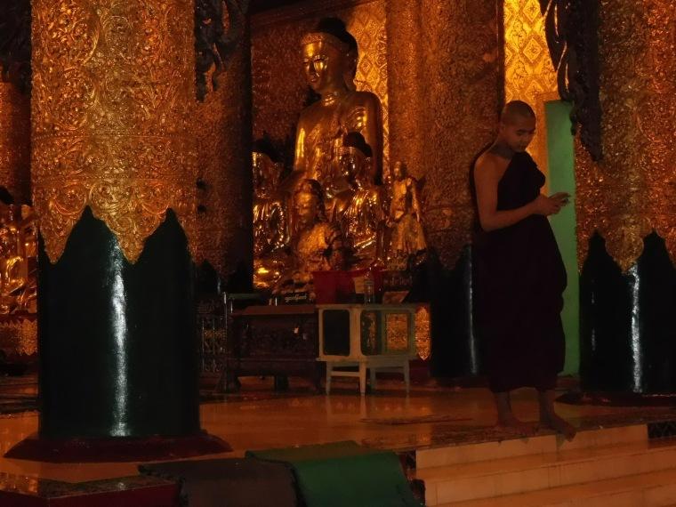 Mönch mit Smartphone vor einer Buddha-Figur bei der Shwedagon Pagode in Yangon, Myanmar/Burma