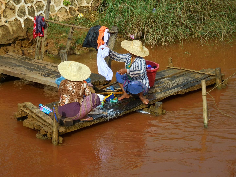 Zwei Burmesinnen waschen Wäsche in braunem Wasser. Myanmar/Burma