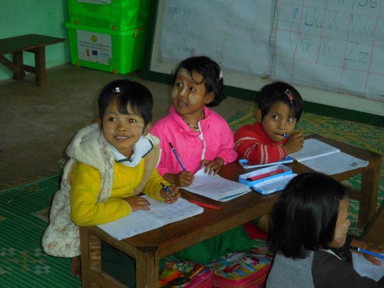 3 Kinder sitzen in einer burmesischen Schulbank