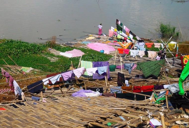 Wäscheleinen mit bunten Kleidungsstücken direkt am Ufer des Irrawaddy in Mandalay, Myanmar/Burma