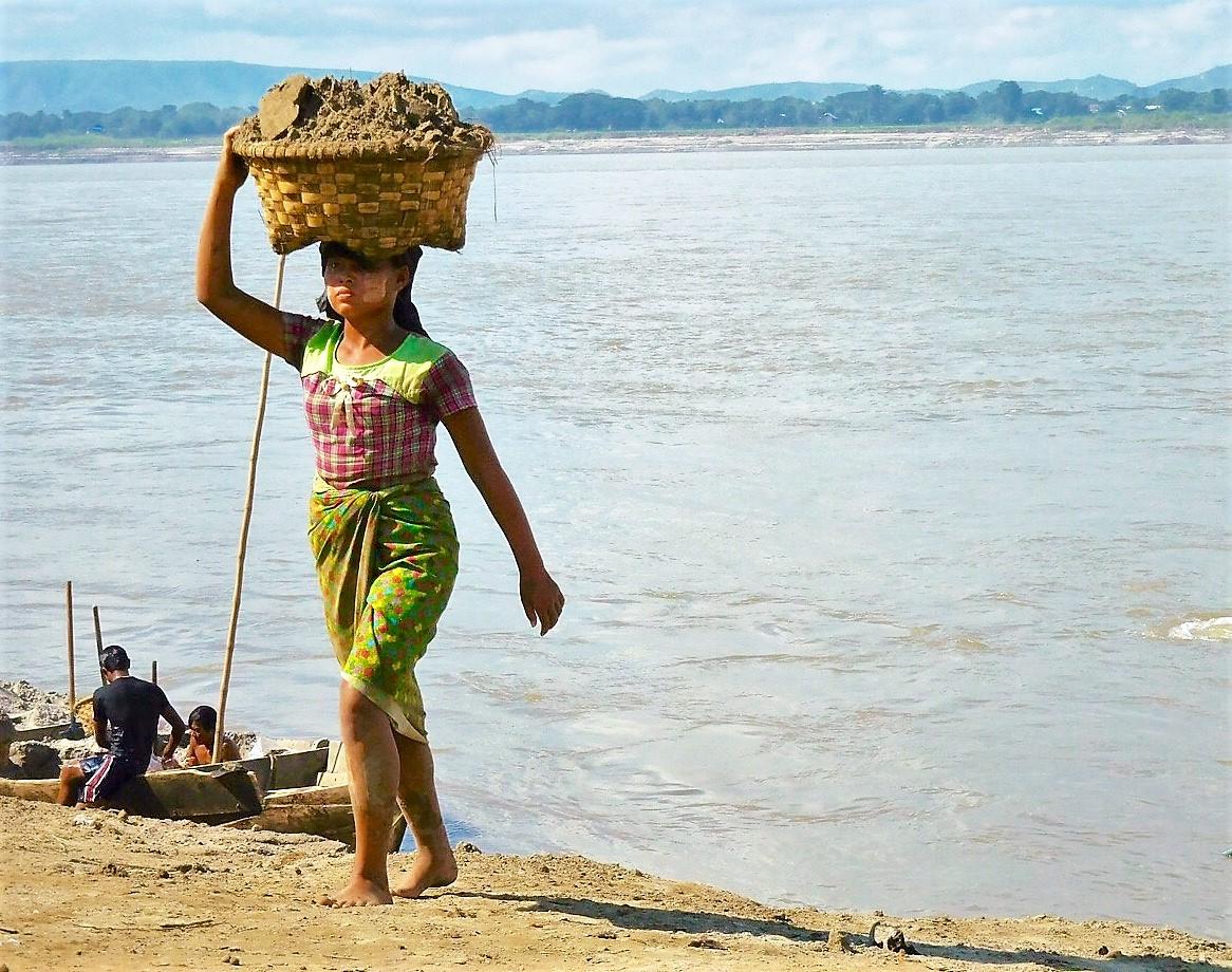 Eine Burmesin trägt einen Korb mit Sand auf dem Kopf