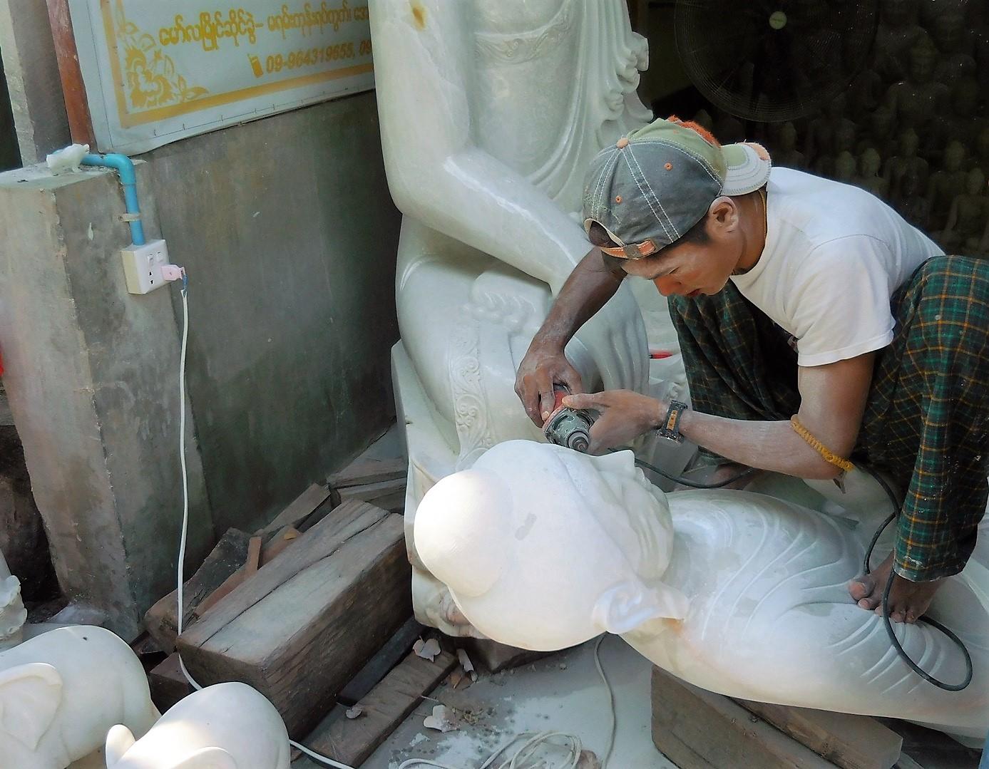 Ein Burmese bearbeitet eine Buddha-Figur aus Marmorstein