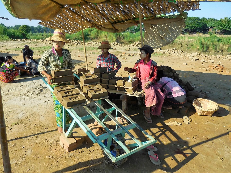 Eine Burmesin fährt mit einer Schubkarre die Lehmsteine zum Trocknen