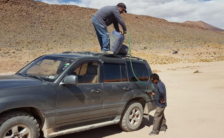 Das Auto wird in der Wüste aufgetankt.